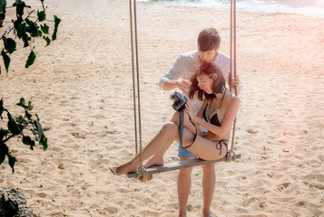 couple lover sitting on wooden swing at the seabeach, enjoy photo on camera after shot taken honeymoon, valentine holidays vacation enjoyment