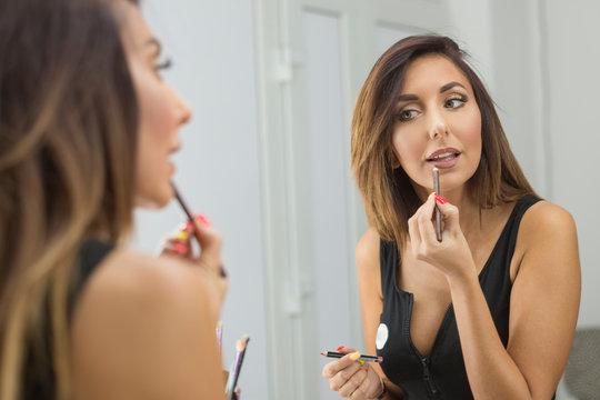 Beautiful young woman applying lip-liner pencil.