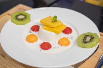 Panna Cotta with Watermelon, Melon, Mango and Kiwi served on plate