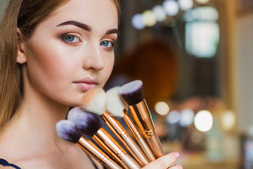 Close up the beautiful young woman holding the make-up brushes in hand near her face indoors