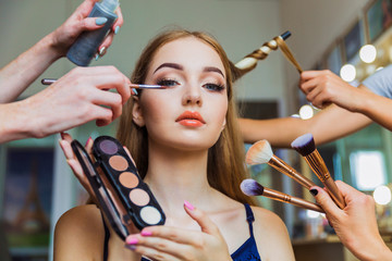 Portrait of the charming young woman who is sitting indoors and makeup artist doing makeup her and hairdresser doing the hairdo her