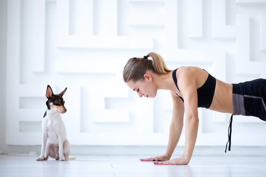 Fitness woman doing exercises with her dog.