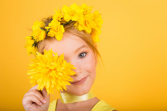 Portrait of a cute girl with freckles and a yellow wreath on her head. A girl in a yellow dress holding a yellow flower