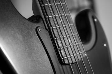 Horizontal detail of the fret board of a bass guitar, on a dark background