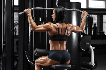 Muscular woman working out in gym doing exercise for back. Strong fitness girl, muscles back
