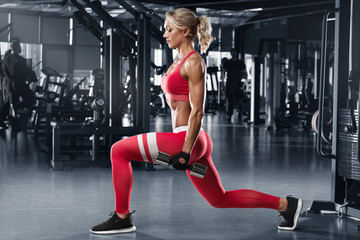 Fitness woman doing lunges exercises for leg muscle workout in gym. Active girl doing front forward...