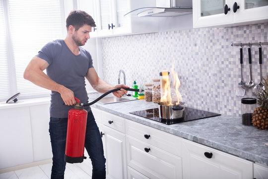 Man Extinguishing Burning Cooking Pot