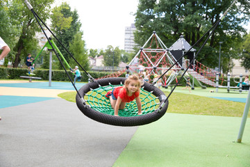 Cheerful girl swinging in the swing-nest