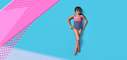Fashion child summer. Little girl kid in swimsuit lay view top. Concept beach vacation. Blank, banner, copy space for ,advertising. Isolated pink, blue color background like sea water in studio.