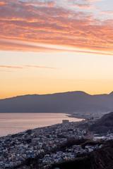 夕暮れの海と山と町