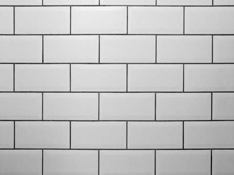 White metro tiles with grey grout. White rectangle tiled background