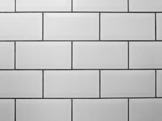 White metro tiles with grey grout. White rectangle tiled background