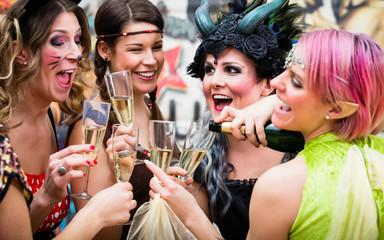 Gruppe von Frauen im Karneval gönnt sich Glas Prosecco am Rosenmontag