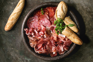 Antipasto meat platter assorti of sliced jamon, salami, chorizo sausage in terracotta tray with bread and greens over dark metal background. Flat lay, space