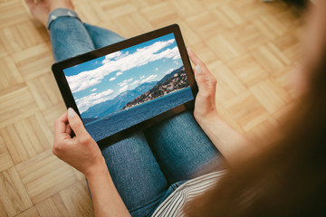 Young girl in blue jeans holding tablet, watching beautiful landscape of summer in Montenegro while sitting on wooden floor.