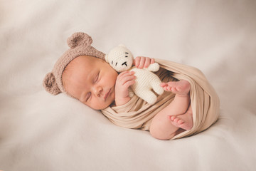 Newborn sleeping boy with a toy in a hat with ears