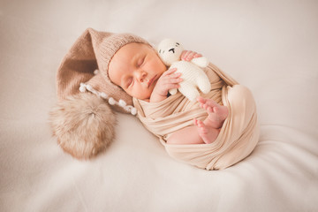 Newborn with a toy on a beige background