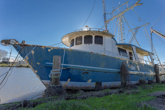 Vintage forgotten ship tied to wooden grassy dock