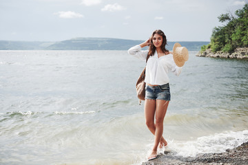 A beautiful young girl in a hat and with a backpack playfully walks by the water. A warm summer day is a great time for adventure and adventure in nature