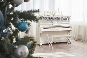 New Year decoration. Christmas tree near white piano at the window background
