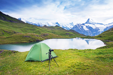 Tent and camera on a tripod in the mountains in the Swiss Alps, Europe (still life coach, company, friendship, background - concept)