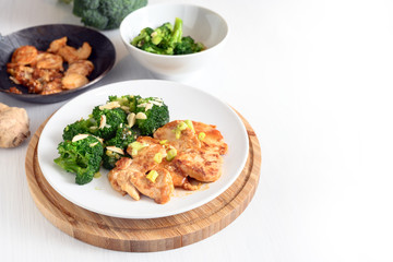 chicken breast fillet and broccoli with ginger on a green napkin and rustic wooden table, copy space, selected focus, narrow depth of field
