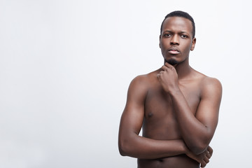 Portrait of handsome unshaven dark skinned male holds chin, dressed in jeans, poses shirtless, looks seriously at camera, isolated on white background. People, ethnicity and facial expressions concept