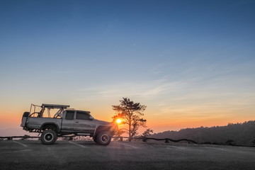 sunset at Huai Nam Dang National Park, beautiful silhouette of a 4x4 truck parking on the road with colorful red light in the sky background, Huai Nam Dang in Chiang Mai, northern of Thailand.