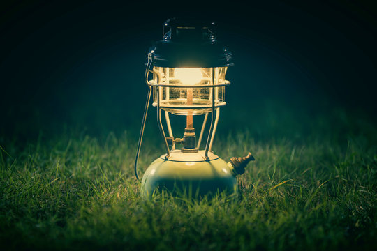 Old lantern On the lawn at night.Vintage colors picture.