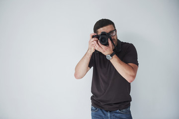 A young hipster man in eyepieces holds a DSLR camera in hands standing against a white wall background