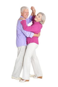 Portrait of happy senior couple dancing on white background