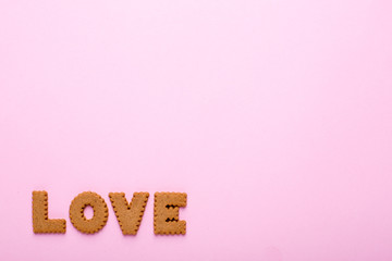 Letters tasty cookies Love on pink background