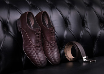 Men's shoes and belt. Elegant men's leather shoes and belt on a black leather sofa.