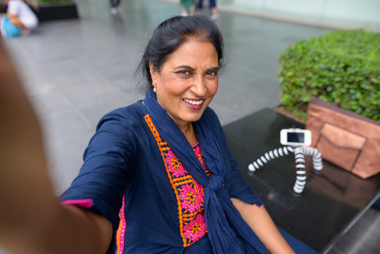 Personal point view of mature Indian woman taking selfie