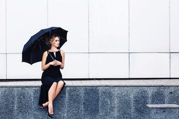 gorgeous woman with an umbrella sits on the parapet and waits.