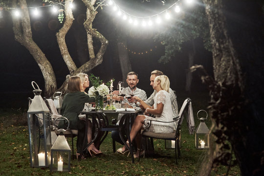 Beautiful garlands create a sense of fairy tale. Group of adult friends have a rest and conversation in the backyard of restaurant at evening time