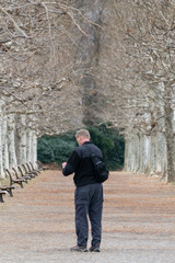 Old man walking and taking photos of withered tree lined avenue with benches in a park (Winter of Tokyo, Japan)