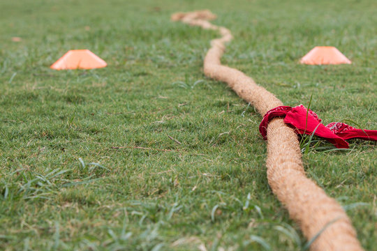 Tug Of War Rope With Bandana Attached Lies On Grass