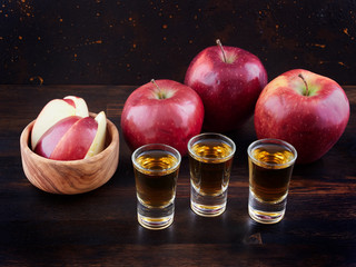 Aged apple brandy or Calvados and red apples, on a dark wooden board, with a dark brown background