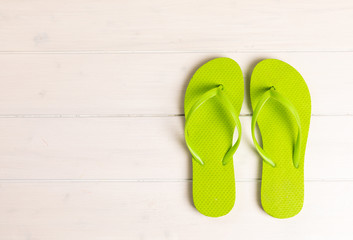 green flip flops on white wooden background with copy space