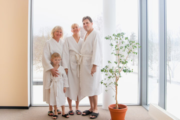 Happy big family: mom, dad, son, grandma in bathrobes enjoying their vacation at a spa resort.