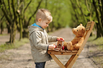 A lovely, smiling boy sitting on the chair with teddy bear at the springtime. Hazel tree