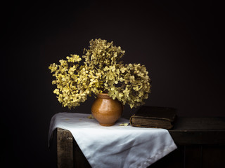 Dramatic chiaroscuro style photo of dried hydrangea flowers with old book on dark background. Melancholy still life with copy space.