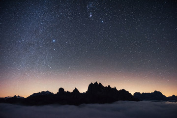 Beautiful space filled with stars in the sky. The mountains are surrounded by dense fog