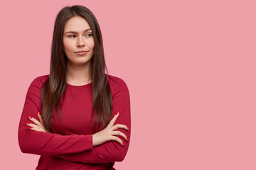 Photo of thoughtful brunette young woman with dark hair, keeps arms folded, considers something in mind, wears red sweater, stands against pink background. People, thoughts, considering concept