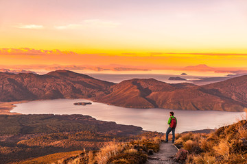 Hiking wanderlust adventure man hiker alone looking at sunset nature landscape of mountains and lakes during summer. Travel outdoors freedom lifestye.