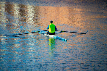 man in yellow vest trains on a racing sculling boat in Oxford