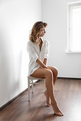 Sexy girl in white shirt on a white Chair