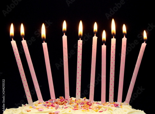 A Close Up Photograph Of Frosting On Cake With 10 Candles Lit Against Black Background 10th Birthday Concept Years Old Year Anniversary