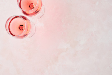 Summer drink. Glass of rose wine on pink background with copy space for text. Top view.